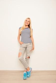 Jovem mulher muito elegante posando de jeans rasgado