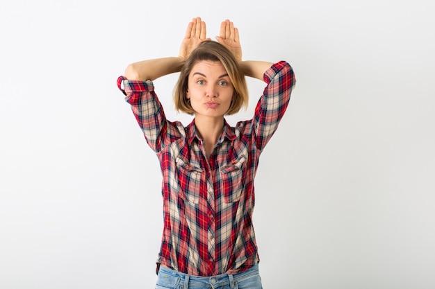 Jovem mulher muito engraçada e emocional com camisa quadriculada posando isolada na parede branca do estúdio, mostrando gesto de coelho