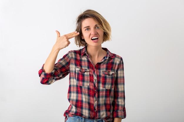 Jovem mulher muito engraçada e emocional com camisa quadriculada posando isolada na parede branca do estúdio, mostrando o gesto da arma
