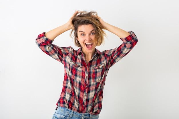 Jovem mulher muito engraçada e emocional com camisa quadriculada posando isolada na parede branca do estúdio, mostrando um gesto maluco