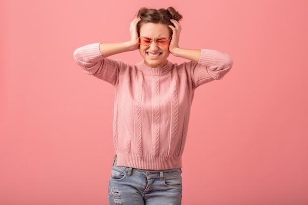Jovem mulher muito engraçada tendo um problema, sentindo dor de cabeça, estresse e segurando a cabeça dela, com um suéter rosa e óculos de sol isolados no fundo rosa do estúdio