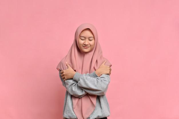 Jovem mulher muito muçulmana se sentindo apaixonada, sorrindo, acariciando e abraçando a si mesma, permanecendo solteira e egocêntrica contra um fundo rosa.