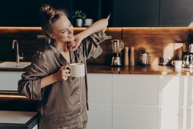 Jovem mulher muito relaxada em um pijama confortável, estendendo-se do sono no início da manhã, segurando uma xícara de café na mão, de pé no interior da cozinha elegante. tempo médio de lazer em casa