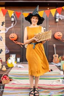 Jovem mulher muito sorridente com um vestido elegante e um chapéu preto segurando uma cesta com doces enquanto espera as crianças de halloween na escada perto da porta