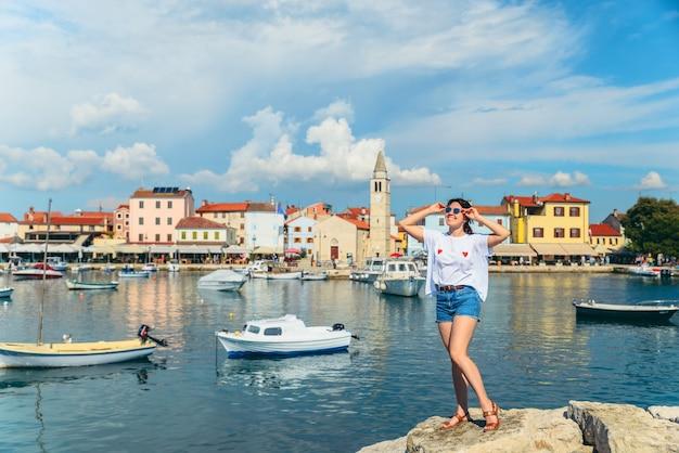 Jovem mulher muito sorridente em pé na cidade de fazana praia no fundo. croácia