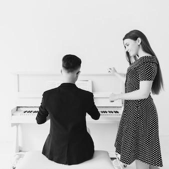 Jovem mulher muito sorridente, olhando para o homem tocando piano