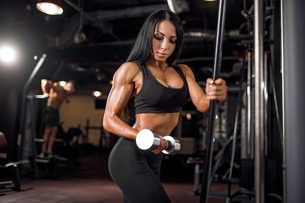 Jovem mulher muscular fazendo exercícios na academia