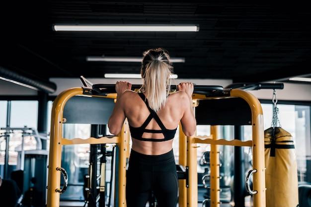 Jovem mulher muscular fazendo puxe o exercício no ginásio.