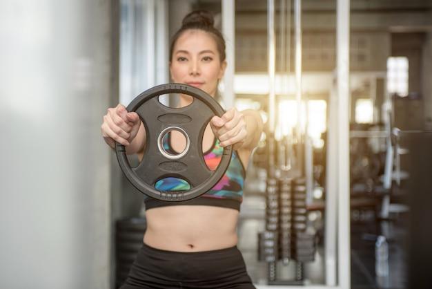 Jovem mulher muscular que levanta peso no gym.