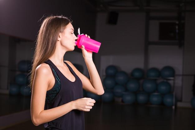 Jovem mulher musculosa bebendo nutrição esportiva