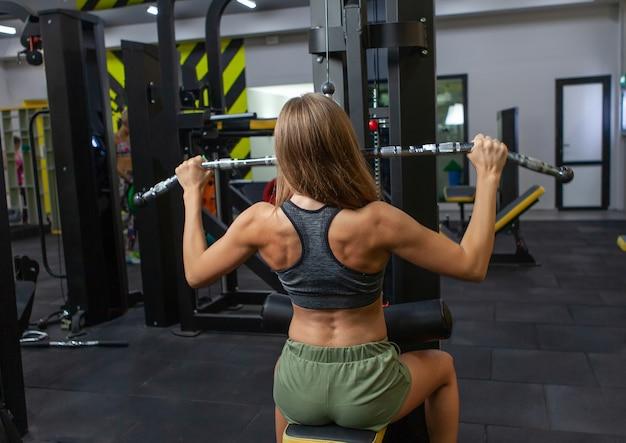 Jovem mulher musculosa fazendo exercício de puxar para baixo em uma máquina latina na academia