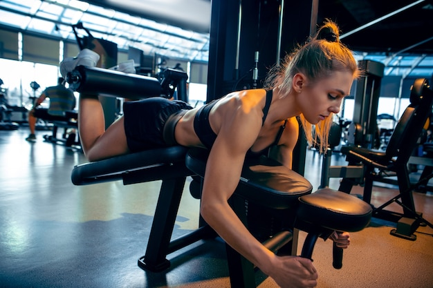 Jovem mulher musculosa praticando academia