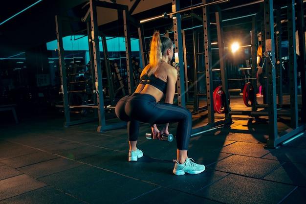 Jovem mulher musculosa praticando na academia com os pesos