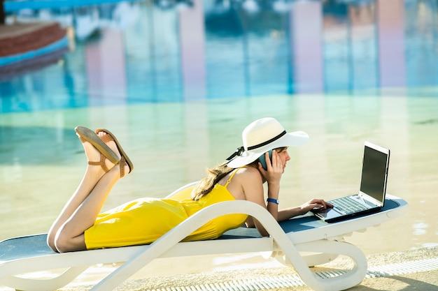 Jovem mulher na cadeira de praia na piscina, trabalhando em um computador laptop e falando no telefone de venda em resort de verão