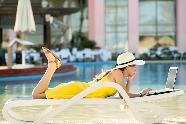 Jovem mulher na cadeira de praia na piscina, trabalhando no computador laptop conectado à internet sem fio, digitar texto nas teclas no resort de verão. trabalho remoto e trabalho freelance durante a viagem de conceito.