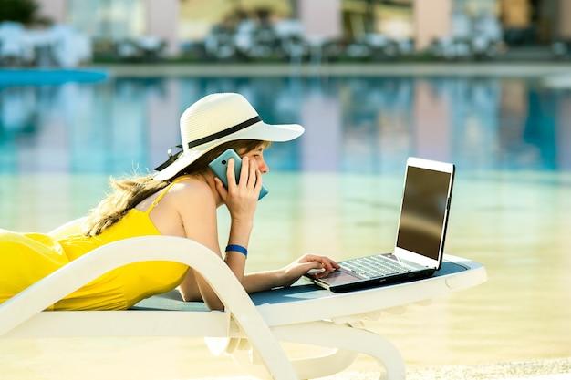 Jovem mulher na cadeira de praia na piscina, trabalhando no computador portátil e falando no telefone de venda na estância de verão. trabalho remoto e trabalho freelance durante a viagem de conceito.