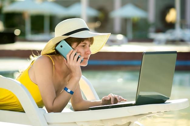 Jovem mulher na cadeira de praia na piscina, trabalhando no computador portátil e falando no telefone de venda na estância de verão.