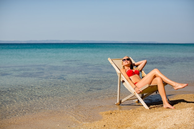 Jovem mulher na cadeira na praia