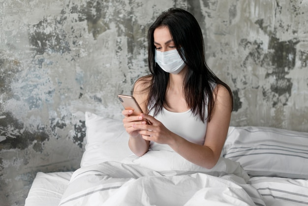 Jovem mulher na cama com máscara facial