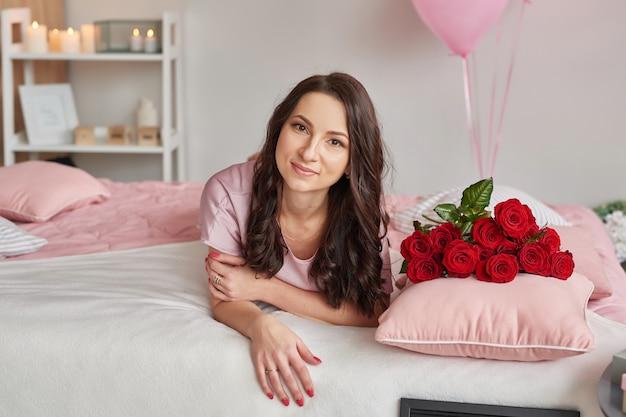 Jovem mulher na cama de pijama rosa com buquê de rosas vermelhas