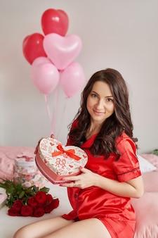 Jovem mulher na cama de pijama vermelho com caixa de presente em forma de coração