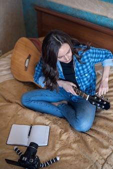 Jovem mulher na cama no quarto afina seu violão e escreve um blog em uma câmera dslr