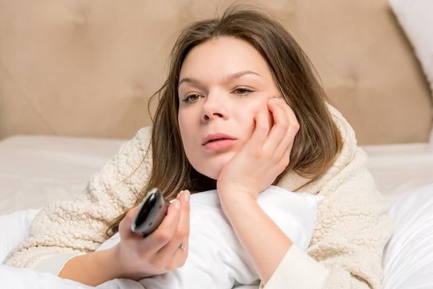 Jovem mulher na cama segurando o controle remoto
