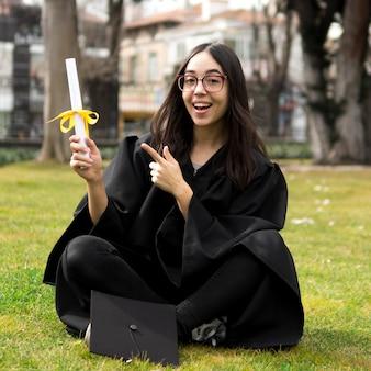 Jovem mulher na cerimônia de formatura, apontando para o diploma