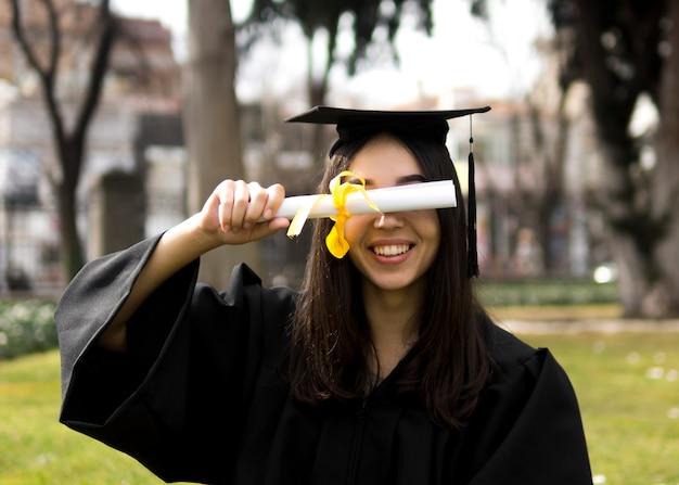 Jovem mulher na cerimônia de formatura, cobrindo os olhos com um diploma