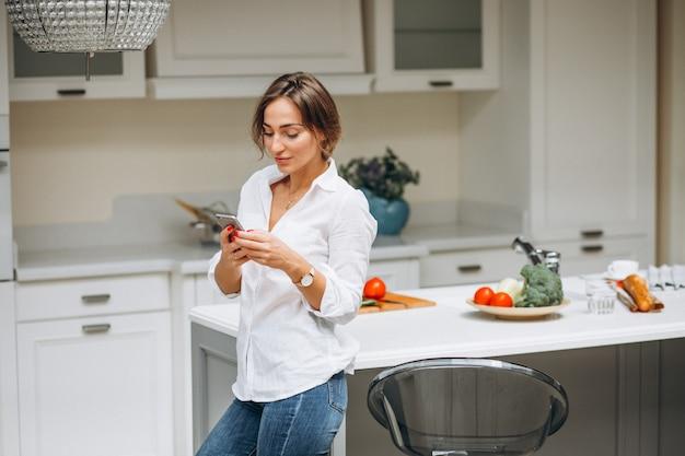 Jovem mulher na cozinha cozinhando o café da manhã e falando ao telefone