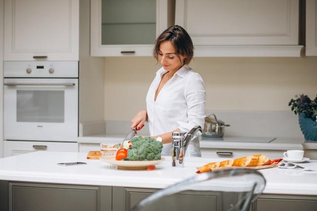 Jovem mulher na cozinha cozinhando o café da manhã