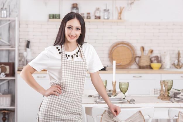 Jovem mulher na cozinha. dona de casa em pé na cozinha. culinária feminina.