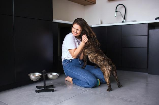 Jovem mulher na cozinha durante a quarentena. menina brincando com seu filhote de buldogue francês. cachorro lambendo a bochecha da mulher. juntos na cozinha.