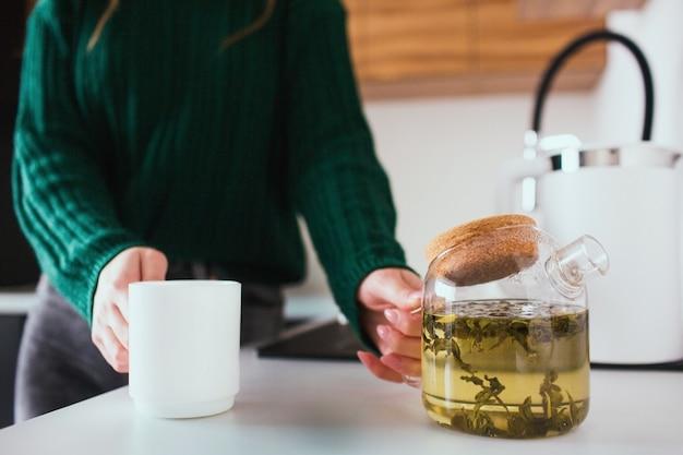 Jovem mulher na cozinha durante a quarentena. menina segura o bule e xícara branca nas mãos. vai servir um chá para o almoço ou jantar.