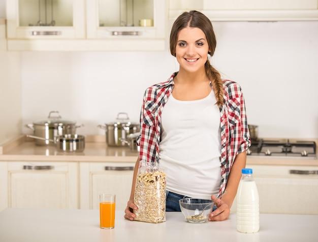 Jovem mulher na cozinha está preparando o café da manhã.