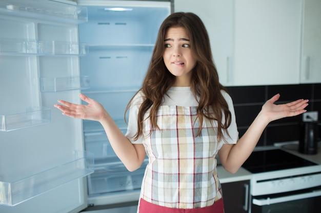 Jovem mulher na cozinha. fique em frente à geladeira aberta e vazia, sem frutas ou legumes. não sabe o que fazer ou cozinhar.