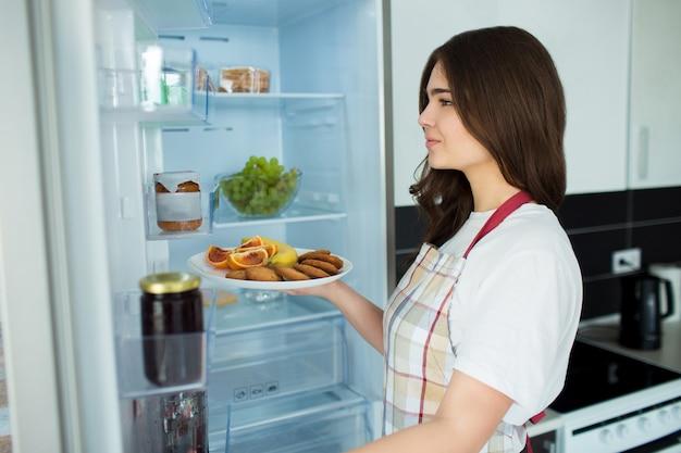 Jovem mulher na cozinha. fique na frente da geladeira aberta e segure o prato com frutas, frutas cítricas e biscoitos. pronto para cozinhar.