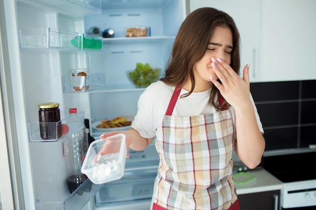 Jovem mulher na cozinha. segure a bandeja de pés plasti aberta com cheiro de cama. comida não fresca. mulher sentir-se mal por causa do cheiro da cama. fique na frente da geladeira aberta.