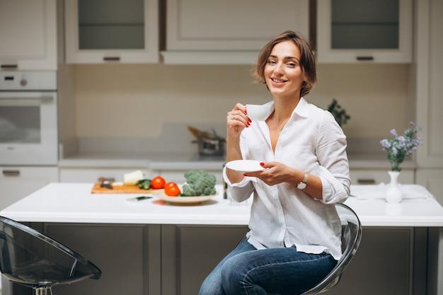 Jovem mulher na cozinha, tomando café da manhã