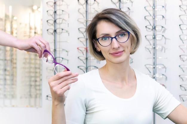 Jovem mulher na loja de ótica, escolhendo novos óculos com oculista. óculos na loja de ótica. uma mulher escolhe óculos. emoções. oftalmologia.