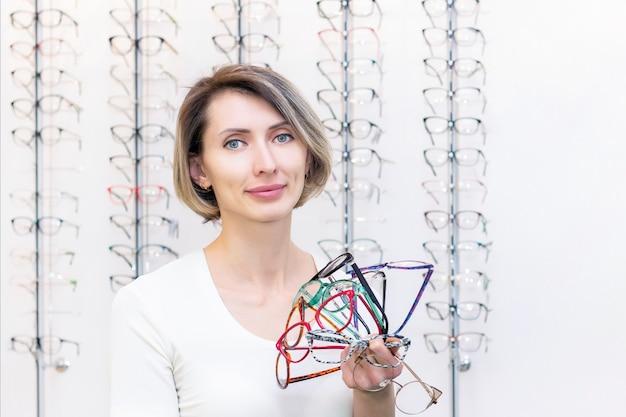 Jovem mulher na loja de ótica, escolhendo novos óculos com oculista. óculos na loja de ótica. uma mulher escolhe óculos. muitos copos na mão. oftalmologia.