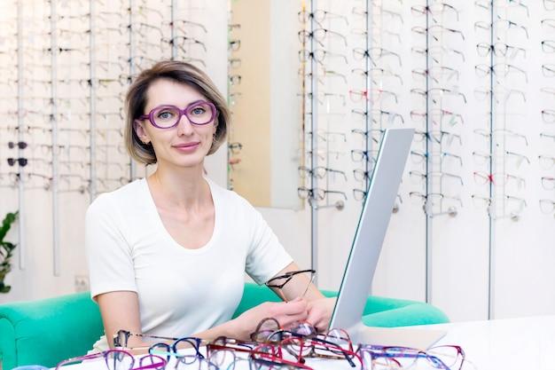 Jovem mulher na loja de ótica, escolhendo novos óculos com oculista.