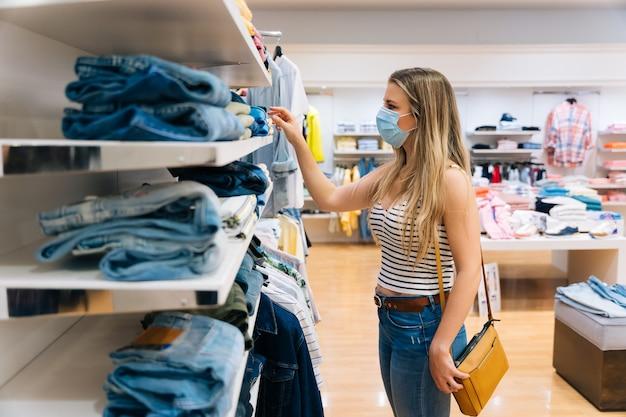 Jovem mulher na máscara de compras em uma loja de roupas na pandemia de coronavírus