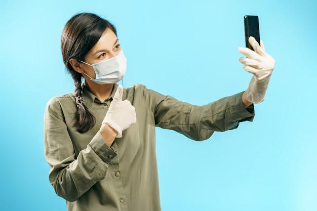 Jovem mulher na máscara médica protetora e luvas fazendo selfie ou vídeo chamada usando smartphone aparecendo polegar em azul.