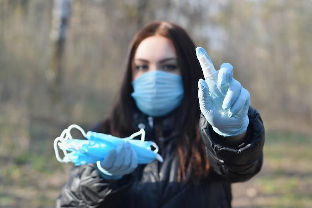 Jovem mulher na máscara protetora mostra frascos de spray desinfetante e máscaras protetoras ao ar livre em madeira de primavera