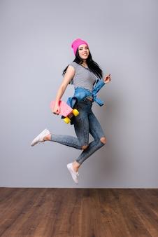 Jovem mulher na moda em jeans e chapéu rosa segurando um skate e pulando no espaço cinza