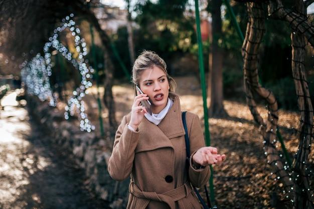 Jovem mulher na moda que fala no telefone esperto no parque da cidade.
