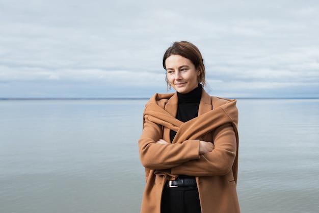 Jovem mulher na moda vestida com casaco de lã bege sorrindo, caminhando na praia