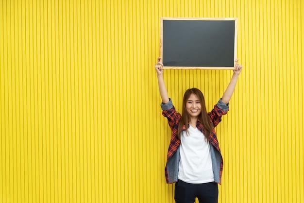 Jovem mulher na mostra ocasional um quadro-negro vazio na parede amarela com sorriso.