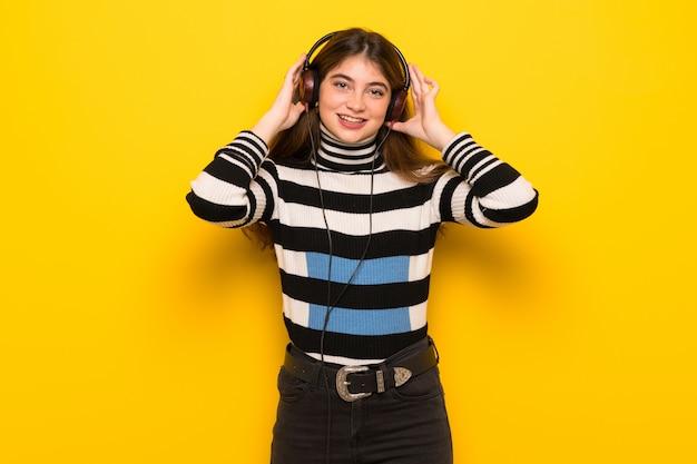 Jovem mulher na parede amarela, ouvindo música com fones de ouvido
